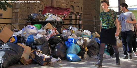 Tourists walk past uncollected garbage in Athens. Pic courtesy of washingtonexaminer.com
